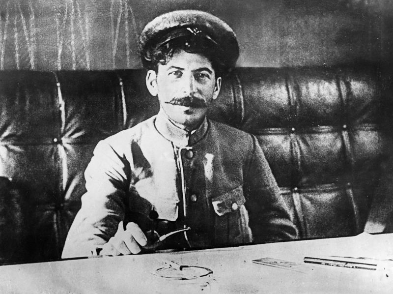 Joseph stalin sitting at a table in 1918.